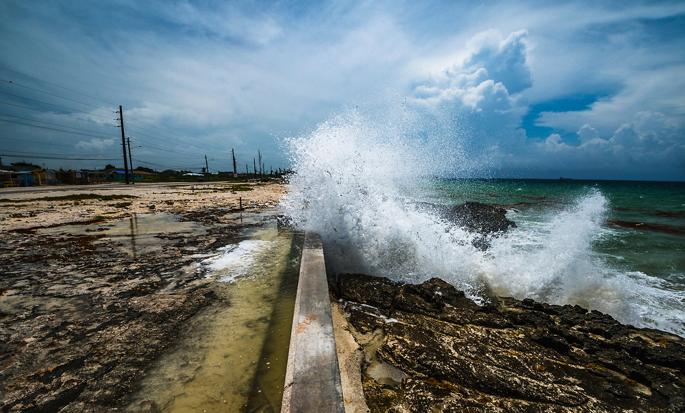 A wave breaks over a seawall on the south shore of Grand Bahama Island. As climate change worsens and sea levels rise protecting coast lines will become a major issue.