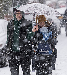 © Licensed to London News Pictures. 24/01/2021. London, UK. A coupe and their young child battle through heavy Snowfall on Hampstead Heath in Hampstead in north London. Parts of the UK continue to suffer from flooding caused by Storm Christoph. Photo credit: Ben Cawthra/LNP