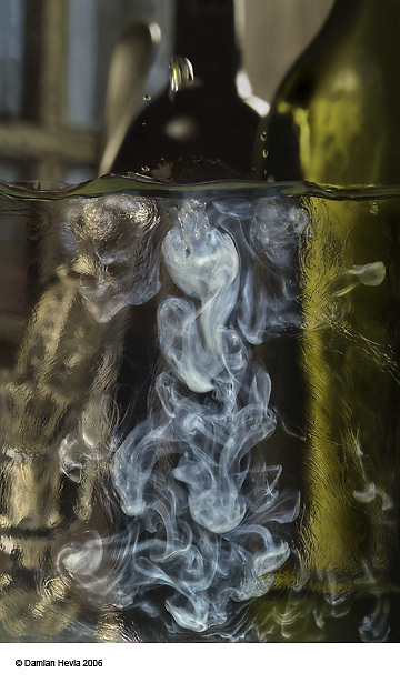 """Photographic capture of the exact moment ice water meets with absinthe causing a chemical reaction called louche which turns clear absinthe into an opaque green liquid. Smoke-like, wavy, oily appearance inside absinthe. A green and black bottle behind reaction. Drops splashing above meniscus. This photograph is published in David Nathan- Maister's, """"Encyclopedia of Absinthe"""". World renowed photograph by Damian Hevia."""
