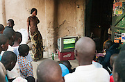 People crowd around a television showing a soccer game, where Mali are playing in the African Nations Cup tournament, Djenné, Mali