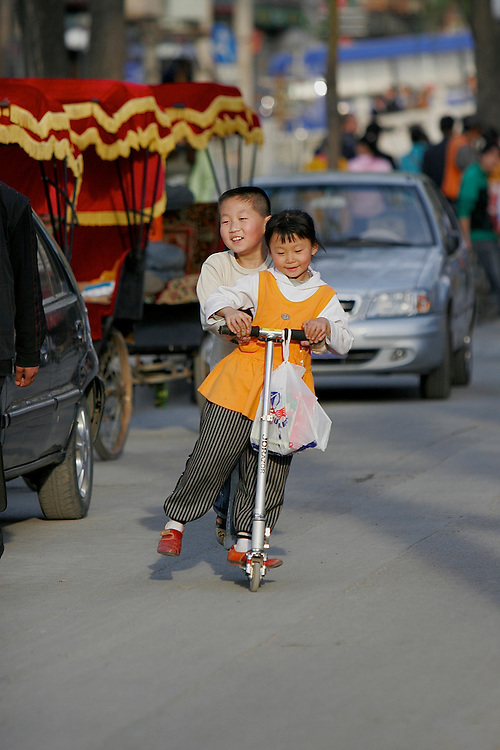 Kids zoom down a side street parallel to the Houhai Lake on a scooter in Shichahai area of Beijing,China.
