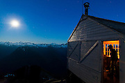 Ethan Welty stands inside the fire lookout cabin on the summit of Hidden Lake Peaks, North Cascades National Park, Washington.