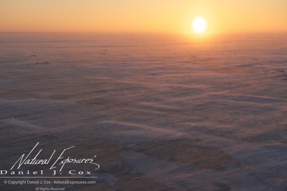 Sun sets over a frozen lake near Churchill, Manitoba.