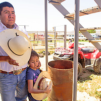 Johnyatte and his Jaynette Begay, 7, wait and listen to the cowboy invocation before the start of a rodeo in Pinedale.