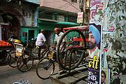 Rickshaws and a political poster on the street in Sitaram Bazar, Old Delhi, India