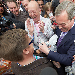 © Licensed to London News Pictures.  30/04/2015. AYLESBURY, UK. Nigel Farage (right), UKIP party leader, receives a gift from a supporter during a campaign visit to Aylesbury. <br /> <br /> Also in this picture: Chris Adams (centre left in light jacket), UKIP candidate for Aylesbury.<br /> <br /> Photo credit: Cliff Hide/LNP