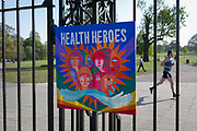 As the UK governments lockdown restrictions during the Coronavirus pandemic continues, and number of UK reported cases rose to 138,078 with a total now of 18,738 deaths, a runner passes behind a home-made piece of art celebrating NHS National Health Service care worker heroes <br /> attached to the gates of Brockwell Park, a public green space in the south London borough of Lambeth, on 23rd April 2020, in London, England.