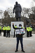 Kill the Bill demonstration in Central London against the proposed Police, Crime, Sentencing and Courts Bill on the 3rd April 2021, London, United Kingdom. Police officers protecting the Churchill statues in Parliament Sqaure. A protester with a Kill the Bill poster. After the protest ended in Parliament Square police cleared the streets, arresting several in the process. Thousands turned out in London and across the UK to show their objection to the Governments proposed bill. Many fear the bill is meant to suppress acts of protesting and demonstrations. The police will be given greater powers to prevent and stop actions of civil disobedience and peaceful protests and many see this as a suppression of their civil liberties. Sentencing for acts of peaceful protest is also likely to be much harsher and that may also act as a deterrent to protest.