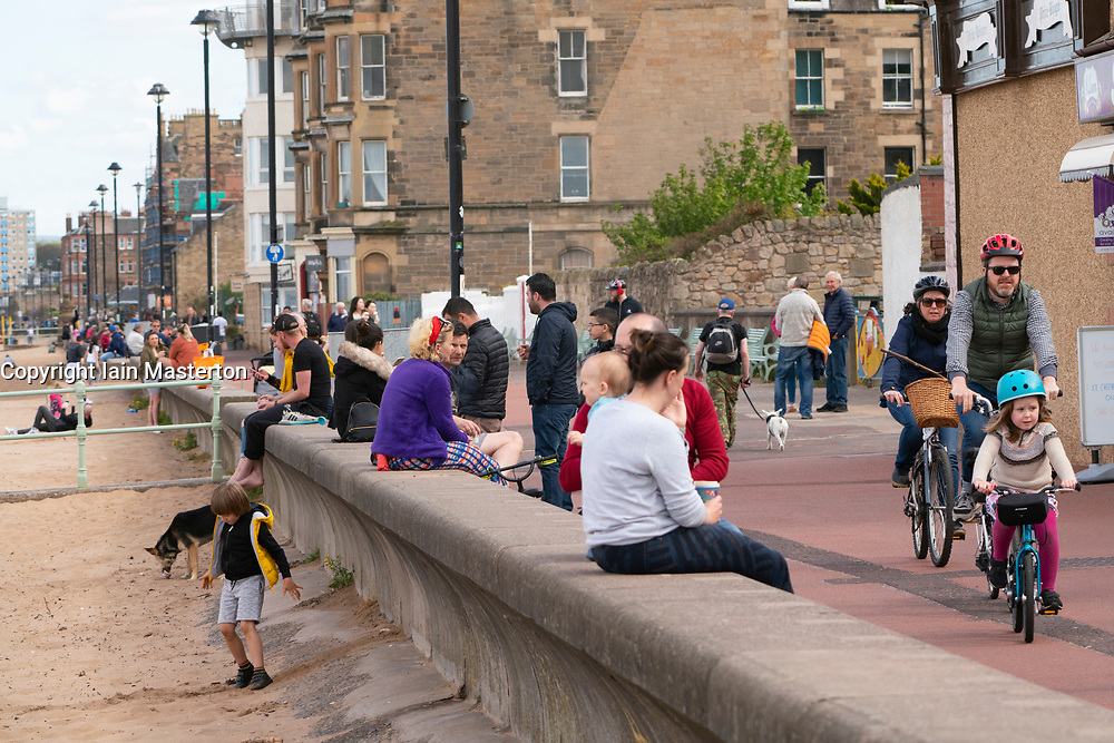 Portobello, Scotland, UK. 11 May 2020. Late afternoon views of popular Portobello beach and promenade. Despite occasional police patrols, the public were determined to relax and enjoy sitting in the sunshine. Promenade busy with people relaxing and exercising.  Iain Masterton/Alamy Live News