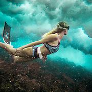 Female Freediver swimming under waves near Kailua Kona, Big Island, Hawaii.