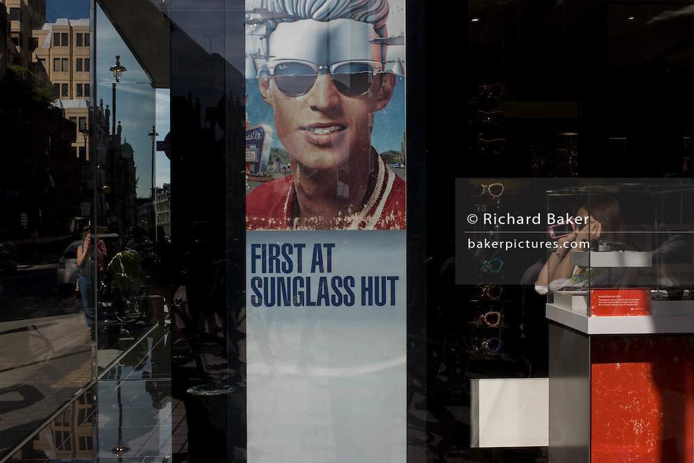 A woman shopper tries on a pair of sunglasses with a poster of a model showing stylish shades outside a sunglasses shop window selling Ray Bans on Long Acre in London's Covent Garden.