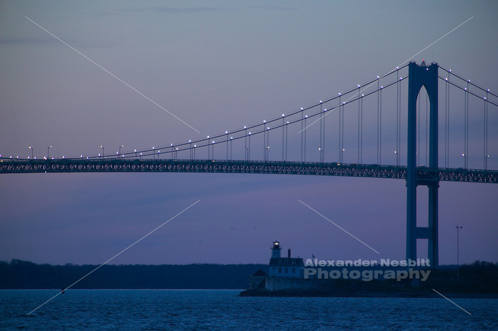 USA - Newport, RI - Newport Pell Bridge and Rose Island lighthouse at dusk.