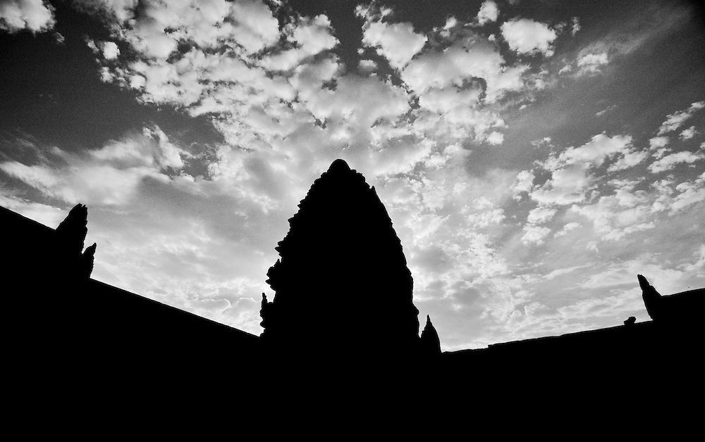This Black and White shot of Angkor Wat, the world's largest single religious monument was shot inside the interior of the main towers of the complex.<br /> <br /> Angkor Wat was built for the king Suryavarman II in the early 12th century as his state temple and capital city.<br /> <br /> It is a massive three-tiered pyramid crowned by five lotus-like towers rising 65 meters from ground level is surrounded by a moat and an exterior wall. All the walls of the temple are covered inside and out with bas-reliefs and carvings. <br /> <br /> The ruins of Angkor, a UNESCO World Heritage Site with temples numbering over 1000, are hidden amongst forests and farmland to the north of the Tonle Sap Lake outside the modern city of Siem Reap, Cambodia. <br />  <br /> It is one of the most awe-inspiring locations I have ever been. From the sunrise to the sunset, there isn't a time of day that is not simply a spectacular time to explore this breathtaking location.