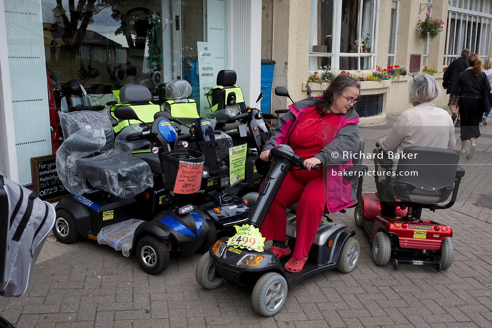 Disabled ladies practice driving Shoprider mobility scooters outside a retailer, on 14th July 2017, at Scarborough, North Yorkshire, England.
