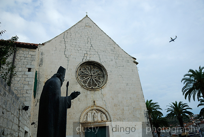 Statue of Bishop Augustin Kazotic, with church of Sveti Duje (Saint Dominic) Monastery in background, and aeroplane flying overhead. Trogir, Croatia