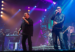 © Licensed to London News Pictures. 11/06/2015. Newport, UK.   UB40 performing live at Isle of Wight Festival 2015, Day 1 Thursday.   In this picture - Astro (left), Ali Campbell (centre).Photo credit : Richard Isaac/LNP