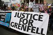 Justice for Grenfell banner at the Peoples Assembly National Demonstration Against Theresa May and Austerity - Not One Day More - Tories Out, on Saturday July 1st in London, United Kingdom. Tens of thousands of people gathered to protest in a march through the capital protesting against the Conservative Party cuts. Following the recent General Election where the Labour Party gained seats, while the Conservative Party lost their majority, the mood in the country has been one where an anti-austerity movement is growing as people become tired with Tory rule.