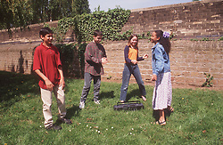Multiracial group of children dancing around stereo in park,