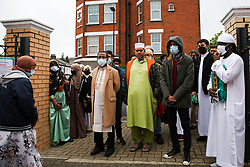 © Licensed to London News Pictures. 13/05/2021. London, UK. Muslim men wearing face coverings queue outside London Islamic Cultural Society and Mosque, also known as Wightman Road Mosque in north London for Eid al-Fitr prayers. Eid al-Fitr or the 'Festival of Breaking the Fast' celebrates the end of the month-long fast of Ramadan, and is being celebrated differently this year as a result of the coronavirus (COVID-19) pandemic. Prime Minister Boris Johnson announced that Covid-19 restrictions on social gatherings, meeting indoors and social contact will ease on May 17, meaning Eid celebrations this week still face restrictions.  Photo credit: Dinendra Haria/LNP