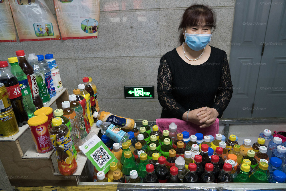 Street vendor seling products near railway station. Everything is cashless and paid by telephone Wechat. She has her WeChat QR card on display in there foreground.