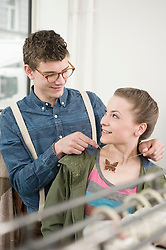 Young man putting necklace around young woman's neck at fashion store