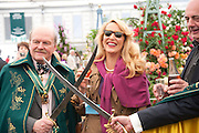 JERRY HALL OPENING CHAMPAGNE BOTTLE WITH A SWORD HELPED BY   MEMBERS OF THE ORDER OF THE GOLDEN SA. The RHS Chelsea Flower Show 2011. The Royal Hospital grounds. Chelsea. London. 23 May 2011. <br /> <br />  , -DO NOT ARCHIVE-© Copyright Photograph by Dafydd Jones. 248 Clapham Rd. London SW9 0PZ. Tel 0207 820 0771. www.dafjones.com.