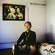 """""""I worked as a militant for the North, which was very important work.  We had to bring rice, weapons, and ammunition to the soldiers in the south.  One day, in June 1968, when we were transporting goods, three US airplanes discovered us and began to shoot at us.  So we took our guns and fired back.  When I shot the first time, I didn't hit the plane.  So I lay down and placed the rifle against the tree and aimed.  When I shot the second time, I shot right at the gas tank, and the whole airplane exploded, and crashed into the next hill.<br /> <br /> """"Then I saw something falling from the sky - I thought it was a bomb, but actually, it was the pilot parachuting down.  So I ran, followed the parachute. When the pilot landed, he had already untied one side of his parachute, but I came and put my gun right to the guy's neck, and said, """"Stay still.""""  He raised his hands, and I told my friends that they should cut up the parachute rope, so we had something to tie him with.<br /> <br /> """"Thirty-six years later, a man from a government office called.  He asked, 'What did you do during the war, did you achieve anything?' After I told him the story, he told me that General Giáp had been looking for me for 36 years.  When I met with him, General Giáp asked me, 'Why are you so good?' and I said, 'It's probably also luck, but I just followed the words I was taught.'<br /> <br /> """"Of course no one wants war.  The life of the human being is sacred.  You don't want the war, you don't want to fight, but when the enemy comes you have no choice. We had to protect our country, had to protect the life of our people.""""<br /> <br /> Ngo Thi Thuong, born 1946, photographed in her bedroom in Hue, Vietnam with a portrait of her with General Võ Nguyên Giáp taken when she was honored for shooting an American F-101 Voodoo in June 1968.  July 2010."""