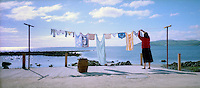 Oh what a beautiful morning! A housewife hangs out her washing at the rear of her Co Antrim cottage on the shoreline between the villages of Carnlough and Waterfoot. Her panoramic view is of the North Channel of the Irish Sea. 19905006921<br /> <br /> Copyright Image from Victor Patterson, Belfast, UK<br /> <br /> t: +44 28 9066 1296 (from Rep of Ireland 048 9066 1296)<br /> m: +44 7802 353836<br /> e: victorpattersonbelfast@gmail.com<br /> <br /> www.images4media.com is the new website which will ultimately replace  www.victorpatterson.com<br /> <br /> Please see my full Terms and Conditions of Use at https://www.victorpatterson.com/page2<br /> It is IMPORTANT that you familiarise yourself with them.<br /> <br /> Images used on the Internet incur an additional cost and must be visibly watermarked i.e. © Victor Patterson or that of the named photographer within the body of the image. The online image must retain all the original metadata. Any changes must be agreed in writing.<br /> <br /> This image is only available for the use of the download recipient i.e. television station, newspaper, magazine, book publisher, etc, and must not be passed on to a third party. It is also downloaded on condition that each and every usage is notified within 7 days to victorpattersonbelfast@gmail.com.<br /> <br /> The right of Victor Patterson (or the named photographer) to be identified as the author is asserted in accordance with The Copyright Designs And Patents Act (1988). All moral rights are asserted.