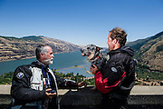Alfonso and Fernando talk about the upcoming kiteboarding at Hood River, Oregon with the Columbia River in the background.  Fernando holds his dog Chano, who travels with Fernando on his BMW R1150GS.