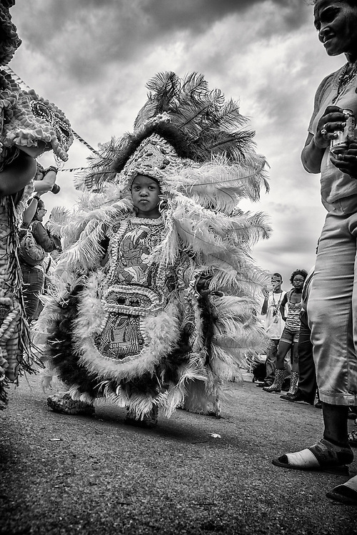 A young member of the Black Eagle, Shawnee and Big Chief Kevin Goodman and Flaming Arrows Mardi Gras Indians parading during the 2013 New Orleans Jazz & Heritage Music Festival at Fair Grounds Race Course on April 28, 2013 in New Orleans, Louisiana. USA.
