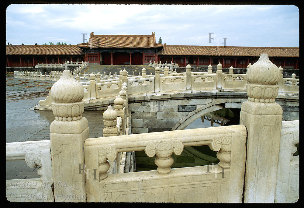 Stone bridges arch across small canal in empty courtyard within the Forbidden City in Beijing. China