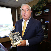 Florida attorney John Morgan holds a photo is his late father Ramon, who passed away from cancer. Morgan has said marijuana helped ease his father's suffering as he was dying of cancer and he believes that legalization in a controlled distribution program is needed by pain sufferers in Florida, and he has provided funding to get a medicinal marijuana ballot measure that would make medical marijuana legal in Florida. This image of him was taken in his office at the Morgan and Morgan law firm in Orlando, Florida on Tuesday, September 2, 2014. (AP Photo/Alex Menendez)