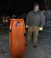 "Time for a hot chocolate by the fire for Bennett and Brian Dean after their sled had a ""blow out"" at the Laconia Parks and Rec Sledding Party Friday evening.  (Karen Bobotas/for the Laconia Daily Sun)"