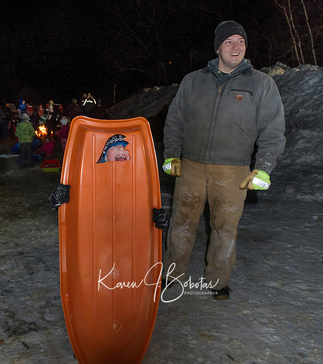 """Time for a hot chocolate by the fire for Bennett and Brian Dean after their sled had a """"blow out"""" at the Laconia Parks and Rec Sledding Party Friday evening.  (Karen Bobotas/for the Laconia Daily Sun)"""