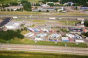 Nederland, Noord-Brabant, Hazeldonk, 04-07-2006;  geparkeerde vrachtauto's bij de grensovergang met Belgie, onder in beeld links een Sheltankstation, rechts een vestiging van hamburgerketen  McDonald's (McDonalds), inclusief rij auto's bij de McDrive; spoorrails in de voorgrond zijn van de HSL; ;opleggers, transport, logistiek, rusttijden, tachograaf, wegverkeer, mobiliteit, rij- en rusttijden, wegverkeer, infrastructuur, verkeer en vervoer, mobiliteit, horeca, fastfood; luchtfoto (toeslag); aerial photo (additional fee required); .foto Siebe Swart / photo Siebe Swart