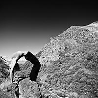 Woman performs Urdhva Dhanurasana yoga position in Big Cottonwood Canyon, Utah