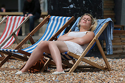 © Licensed to London News Pictures. 20/06/2014. Brighton, UK. A woman sunbathing in a deckchair in the the sunshine on Brighton beach. Warm weather is expected across the UK over the weekend. Photo credit : Hugo Michiels/LNP