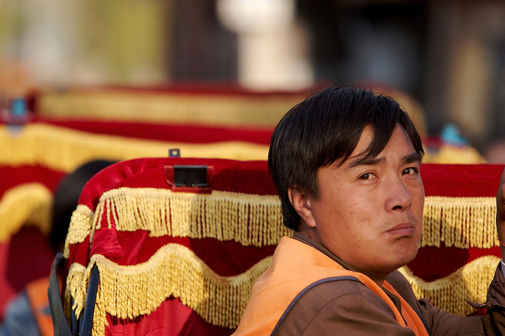 A rickshaw driver takes a break in the early evening waiting for customers by Houhai Lake in Beijing, China.