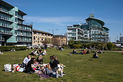 People enjoying some sunny weather socialising at Hermitage Riverside Memorial Garden and overlooking modern glass buildings in Wapping on 17th April 2021 in London, United Kingdom.