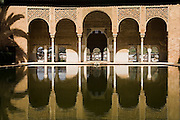 The arches and columns of the Palacio del Partal are reflected in a water pool at La Alhambra, Granada, Andalusia, Spain.