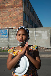 "A young prays, holding her plate, in Parkwood, Cape Town, South Africa, on Sunday, May 31, 2020. The joint prayer in Afrikaans opened a special chicken lunch served by the Parkwood Community Upliftment (PCU) project. The youth organization, which normally feeds children as part of an after-school care program, has been feeding children, the elderly, and many other hungry people, in this poverty-stricken area in the Cape Flats since lockdown started more than two months ago. As the nation moves down to Level 3, on June 1st, CPU founder Max Amansure says the organization will continue to feed people. Often it's ""only"" bread as the organization doesn't have any regular funding. However, as the area has been hard hit by COVID-19, Amansure says he wishes Parkwood could have remained on Level 5 Lockdown. PHOTO: EVA-LOTTA JANSSON"