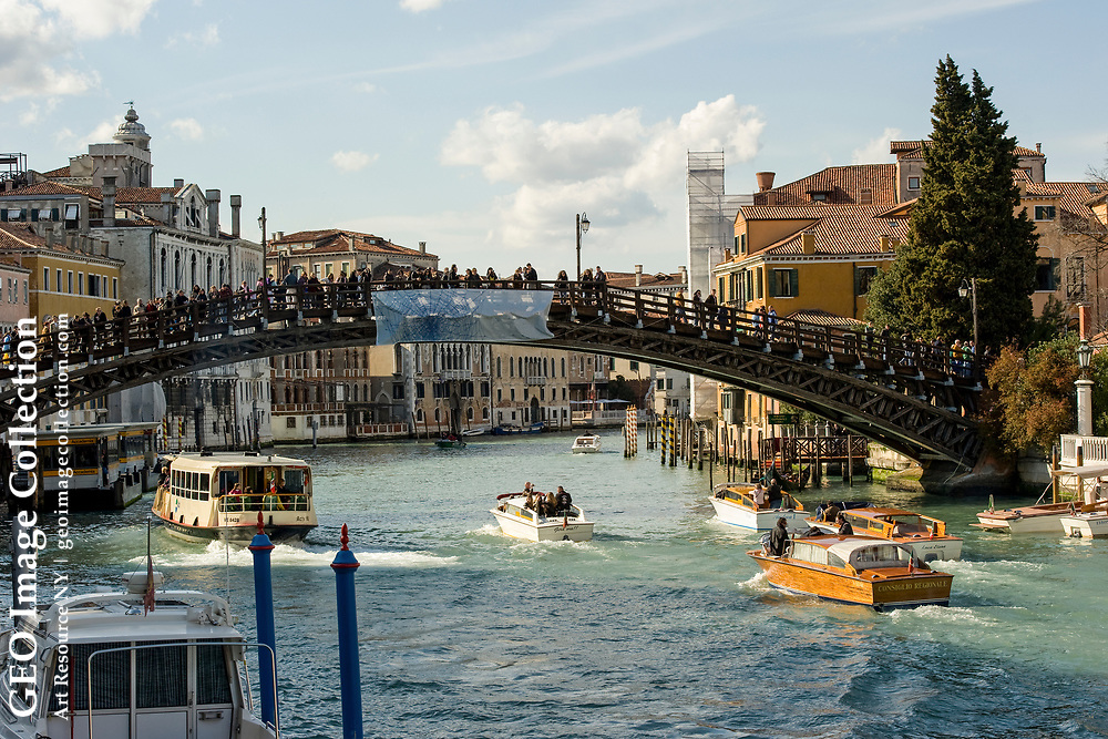 Motorboats speed under the Accademia Bridge, loaded with foot traffic.