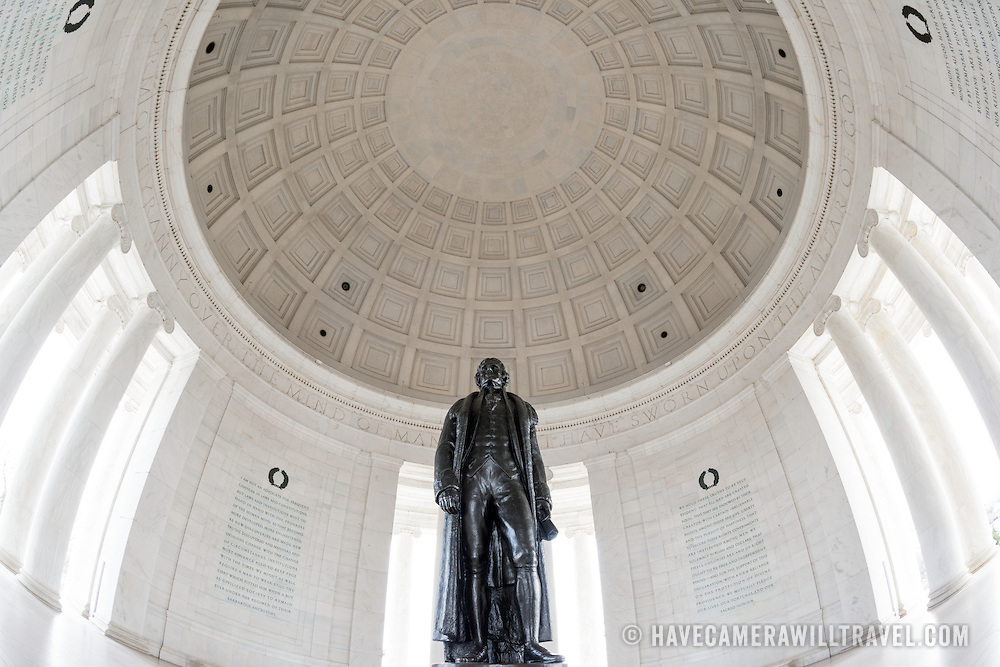 A wide-angle shot looking up at the statue of Thomas Jefferson and the round ceiling at the Jefferson Memorial, on the banks of the Tidal Basin in Washington DC.