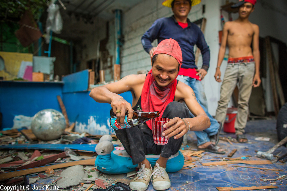"""12 DECEMBER 2012 - BANGKOK, THAILAND:  Demolition workers relax and share a bottle while they drink at the end of their shift in """"Washington Square"""" a notorious entertainment district off Sukhumvit Soi 22 in Bangkok. Demolition workers on many projects in Thailand live on their job site tearing down the building and recycling what can recycled as they do so until the site is no longer inhabitable. They sleep on the floors in the buildings or sometimes in tents, cooking on gas or charcoal stoves working from morning till dark. Sometimes families live and work together, other times just men. Washington Square was one of Bangkok's oldest red light districts. It was closed early 2012 and is being torn down to make way for redevelopment.    PHOTO BY JACK KURTZ"""