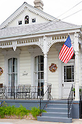 Traditional clapboard creole cottage home with stars and stripes flag in Faubourg Marigny historic district  of New Orleans, USA