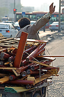 """China, Beijing, Chaoyang, San Jian Fang, 2008. His load complete, a """"furniture man"""" pedals his three-wheel cart away from a profitable day's work. Virtually everything of value business owners did not want in the evictions was recycled."""