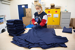 © Licensed to London News Pictures. 17/04/2020. London, UK. A factory worker folds and boxes medical clothing for the NHS (National Health Service) at Fashion-Enter Ltd's factory. The British government continues to try to combat the COVID-19 outbreak, with many garment manufacturers across the country turning to produce medical equipments for the NHS. Photo credit: Ray Tang/LNP