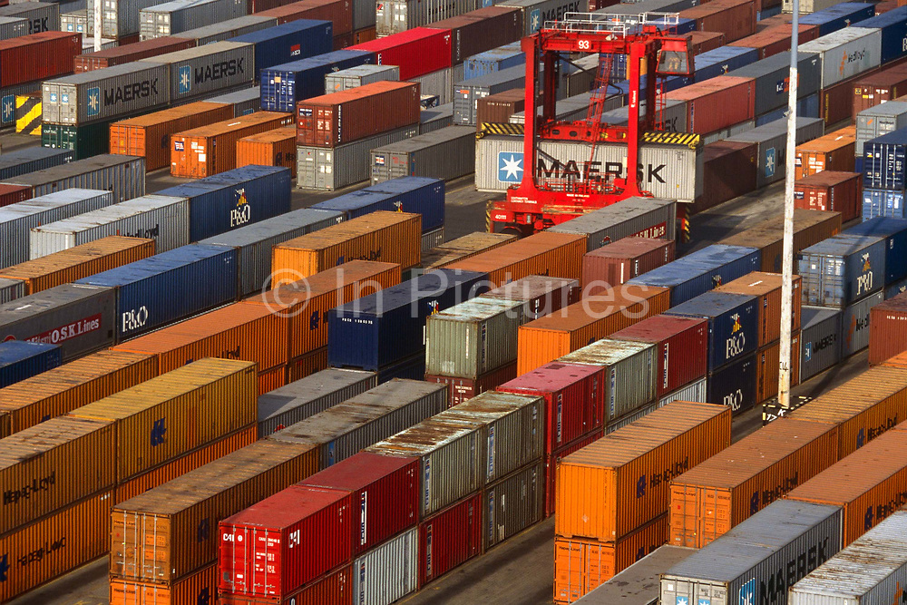An aerial view of cargo shipping containers that are stacked and await shipment to other continents and cities. From this high viewpoint we see a variety of coloured containers bound for countries around the globe, a portable Maersk box being transported across the docks by a lifter vehicle. Others are static, piled on top of each other in a system that revolutionised the way cargo was brought across oceans and continents.