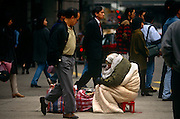 Passers-by ignore destitute bag-lady in Hong Kong's Tsim Sha Tsui street on the Kowloon side.