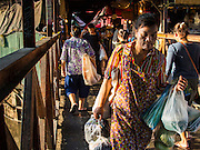19 NOVEMBER 2014 - BANGKOK, THAILAND: Shoppers leave Khlong Toei Market in Bangkok. Between July and September the economy expanded 0.6 percent compared to the previous year, the National Economic and Social Development Board (NESDB) reported. Thailand's economy achieved a weak 0.2 per cent growth across the first nine months of the year. The NESDB said the Thai economy is expected to grow by 1 percent in 2014. Authorities say the sluggish growth is because tourists have not returned to Thailand in the wake of the coup in May, 2014, and that reduced demand for computer components, specifically hard drives, was also hurting the economy. Thailand is the leading manufacturer of computer hard drives in the world. The Thai government has announced a stimulus package worth $11 billion (US) to provide cash handouts to farmers and promised to speed up budget spending to boost consumption.   PHOTO BY JACK KURTZ
